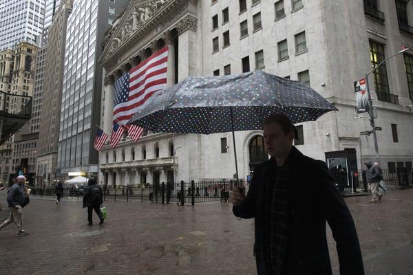 코로나19 확산으로 미국 뉴욕 증시를 비롯한 세계 증시가 폭락하고 있는 가운데 비트코인이 금과 같은 안전자산 구실을 할 수 있을지를 묻는 이들이 많다. 17일 뉴욕증권거래소(NYSE) 앞에서 우산을 쓴 남성이 걸어가고 있다. 출처=AP 연합뉴스